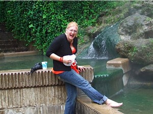 Char dips her foot in the hot springs.