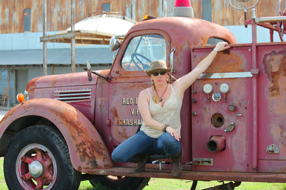 Char poses on a fire truck parked at The Shack Up Inn
